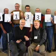 Members of the Penticton & District Stamp Club make a unique donation presentation to the South Okanagan Similkameen Medical Foundation.  Past-president Gus Boersma (sitting at right) greets Foundation executive director Carey Bornn while marking the club's 2016 donation to the Penticton Regional Hospital tower campaign.